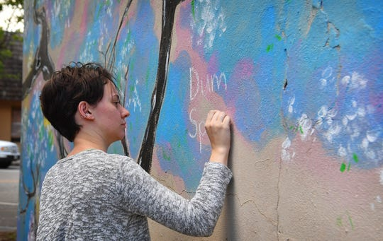 "Alex Lewis writes in Latin, Dum Spiro Spero, or ""While I breathe, I hope"", on the Mural of Hope painted by Gaya Khmoyan at Backdoor Theatre Friday."