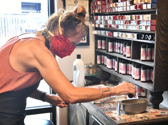 Sherry Potts, a hair stylist at Serenity Salon, mixes hair dye for a client's color job. Barber shops and hair salons were allowed to reopen Friday with social distancing restrictions.