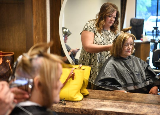 Tammy Carlton, co-owner of Serenity Salon, works on Sandie Herrell's hair Friday morning after hair salons and barber shops across the state were allowed to open with certain restrictions.