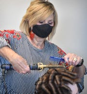 Hair stylist Becky Doyle came back to work at her booth at Serenity Salon Friday morning, after Governor Greg Abbott relaxed restrictions on barber shops and hair salons due to the COVID-19 pandemic.