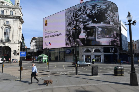 A man walks a dog near a Victory in Europe Day tribute displayed on one of the screens in London's Piccadilly Circus on May 8, 2020 on the 75th anniversary of the end of World War II in Europe.