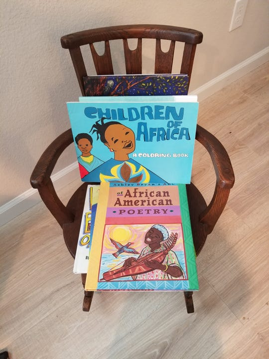"""""""Children of Africa"""" was published by Drum and Spear Press. Daphne Muse, who worked there, is passing it on to her 14-month-old great-grandson Mason who has a library of more than 300 books. The rocking chair belonged to Muse's great-grandmother Daphne Allen when she was a child circa the 1870s."""