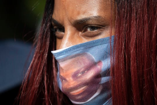 A woman wears a face mask with the likeness of shooting victim Ahmaud Arbery printed on it during a rally on Friday May 8, 2020, to protest Arbery's killing.