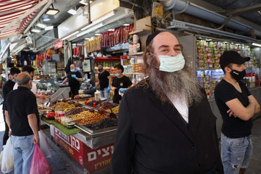 An ultra-Orthodox Jewish man wears a protective face mask as he shops at Jerusalem's Mahane Yehuda market, on May 8, 2020.  Markets and shopping malls have reopened across Israel after temporarily being closed for more than a month in order to prevent the spread of coronavirus, which causes the COVID-19 disease.