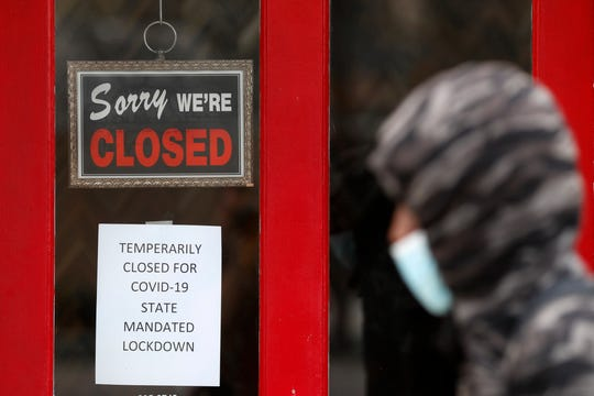 A pedestrian walks by The Framing Gallery, closed due to the COVID-19 pandemic, in Grosse Pointe, Mich., May 7, 2020.