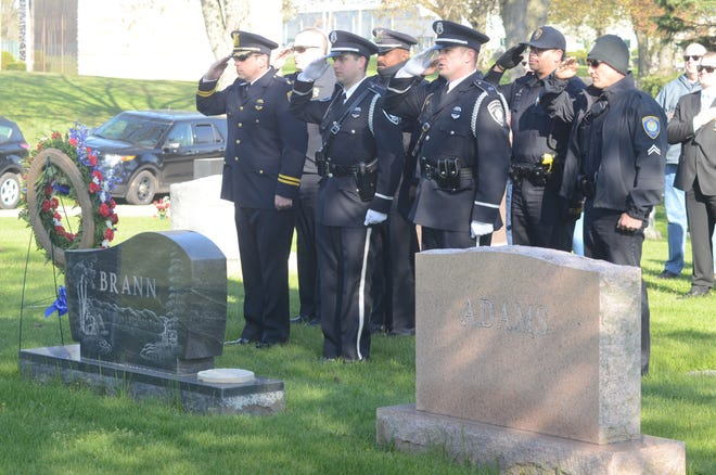 Battle Creek Police Department officers salute at the grave of slain Detective Lavern Brann.  Trace Christenson/The Enquirer