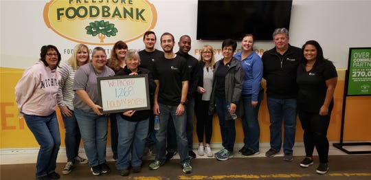 Cornerstone Broker Insurance workers packing holiday boxes for the Freestore Foodbank.