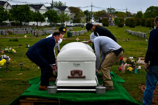 Diocese of Metuchen Chancellor Anthony P. Kearns III, helps to lift the lid of the vault before the casket holding the infants is lowered into the grave at St. Peter's Catholic Cemetery in New Brunswick.
