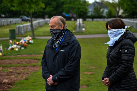 New Brunswick Mayor James M. Cahill stands at the graveside during the rite of committal for the two infants who were abandoned and found hours apart on Feb. 19 at a recycling center in the city.