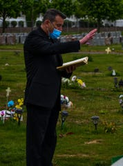 Msgr. Joseph G. Celano, pastor of St. Peter the Apostle University and Community Parish in New Brunswick, presides over the graveside rite of committal for the two abandoned infants buried on May 8 in the parochial cemetery.