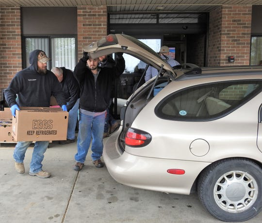 Produce is loaded into the trunk of a participant in the program at the Coshocton Senior Center. The center is continuing with its food distribution and home food delivery programs. Home food delivery has increased from 380 meals a day to 500 since the start of the COVID-19 pandemic.