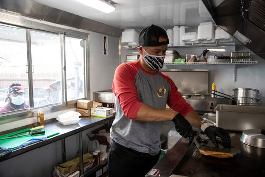 El Cazo food truck owner Gabe Cervantes prepares a Cubano sandwich in Southwest Detroit on May 7, 2020.
