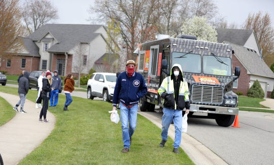 Andrew and Mike Summerhill walk home after ordering food from the Brother Truckers food truck on May 8, 2020.