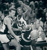 Pistons guard Vinnie Johnson loses the ball after being sandwiched by former Central Michigan player Dan Majerle, left, and former Iowa State player Jeff Grayer of Flint. The pros beat the potential Olympians, 90-83, during an exhibition in 1988.