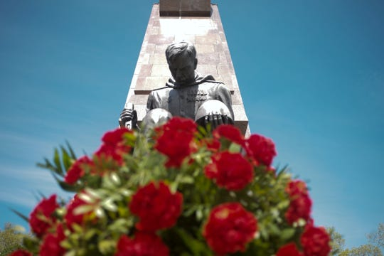 Flowers are placed in front of the statue of a Red Army soldier during commemorations to mark the 75th anniversary of Victory Day and the end of WWII in Europe at the Soviet War memorial at the district Treptow in Berlin, Germany, Friday, May 8, 2020.