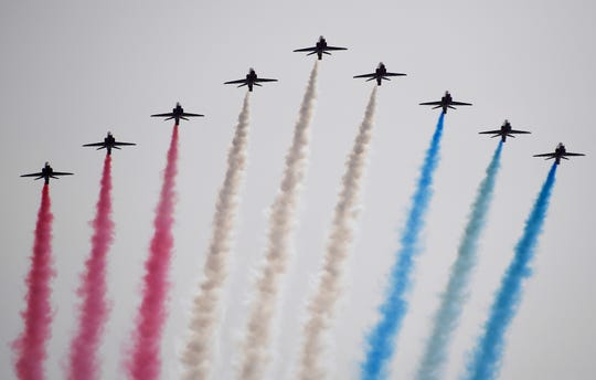 An ambulance worker watches as the Red Arrows, officially known as the Royal Air Force Aerobatic Team flies over Horse Guards Parade in London on Friday, May 8, 2020 on the 75th anniversary of the end of World War II in Europe.