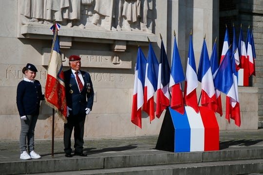 A veteran waits as a girl holds a French flag before a ceremony at a WWI and WWII monument in Lille, northern France, Friday May 8, 2020.