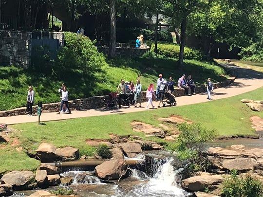 Personas andan en Falls Park después de su reapertura en el 9 de mayo, 2020.