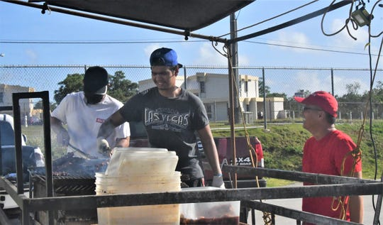 Lawrence Soriano, center, turns skewers of Kris BBQ's pork and chicken May 9 at the new Dededo Flea Market. Saturday marked Kris BBQ's first day back on the grill in more than two months. Overseeing the operation at right is Albert Sanga, supported by his son at left, Albert Sanga Jr. Kris BBQ is offering a free 16-ounce cup of arroz caldo to all frontline workers on weekend mornings throughout May.
