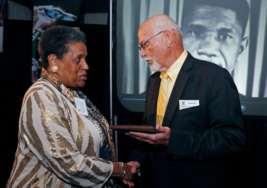 In this April 26, 2014 file photo, Myrlie Evers-Williams, widow of the murdered Mississippi civil rights leader Medgar Evers, receives the 2014 Mississippi Associated Press Broadcasters Pioneers of Television award from retired Jackson, Miss., bureau Associated Press news editor Ron Harrist in Jackson, Miss. Harrist has died at the age of 77 of complications from leukemia. The Mississippi journalist had a four-decade career with the AP, covering Elvis Presley, black separatists, white supremacists and college football legends over the years. (AP Photo/Rogelio V. Solis, File)