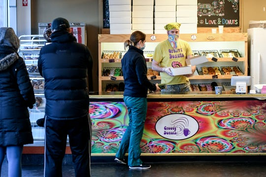 Co-owner Andrew Gauthier, right, helps a customer as others wait in line at Groovy Donuts on Thursday, May 7, 2020, in East Lansing.