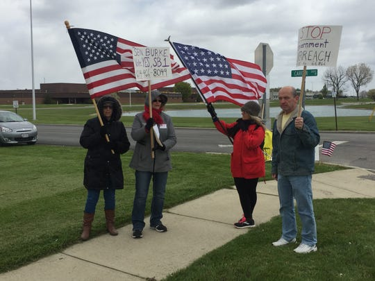 (Left to right) Judith O'Hare, Mary Stoneburner, Victoria Bell and Mark Stoneburner rally in support of reopening Ohio businesses on Saturday outside Tri-Rivers Career Center.