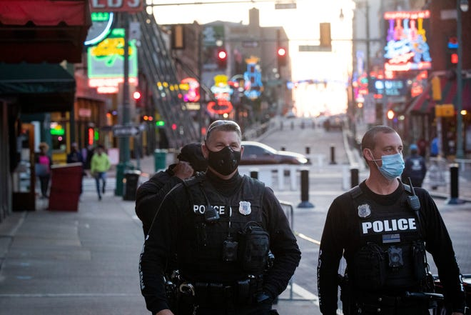 Memphis Police Department officers wear face masks as they patrol Beale Street while establishments slowly reopen on Friday, May 8, 2020.