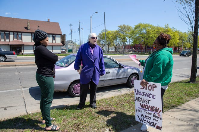 Countessa Lee, from left, Pat Gowens and Nicole Coley talk to each other about advocating for women and ending domestic violence on Saturday near the Walgreens at2727 W. North Ave. A Walgreens worker was shot and killed outside the store Tuesday by an ex-boyfriend, police said.