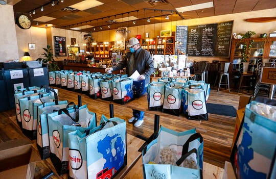 Ken Osmond, owner of Planet Perk Coffee Houses, fills bags of food and essentials May 1 at the City Center location in downtown Oshkosh. The bags will go to those in need who can not get out to local food pantries or grocery stores due to the coronavirus pandemic.