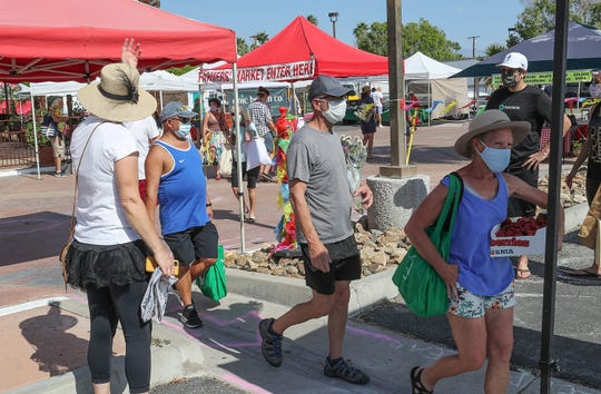 Shoppers leave with their groceries at the Certified Farmers' Market in Palm Springs, May 9, 2020.
