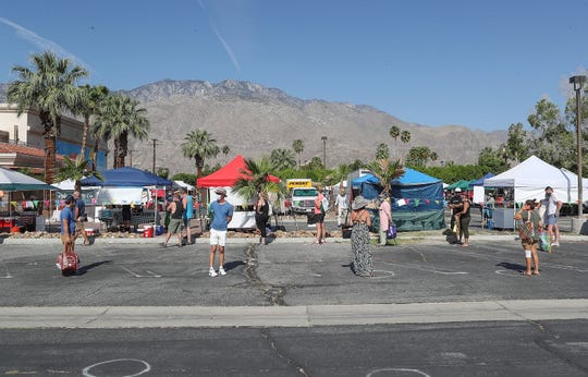 Shoppers practice social distancing while waiting in line to get into the Certified Farmers' Market in Palm Springs, May 9, 2020.