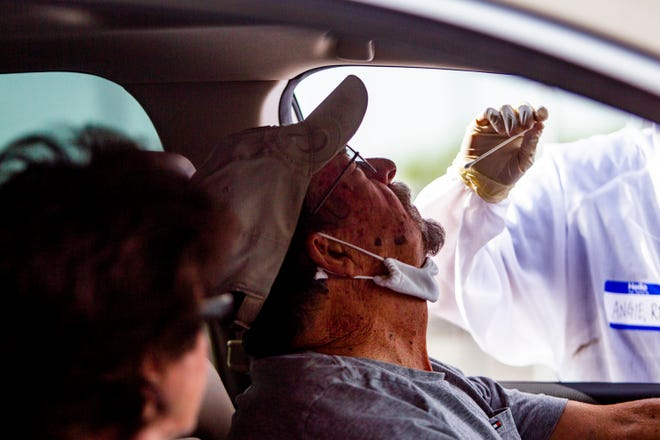 Theodore Lawrence gets tested for coronavirus by a Dignity Health medical worker at a drive-up testing site at State Farm Stadium from Dignity Health and the Arizona Cardinals in Glendale on Saturday, May 9, 2020.