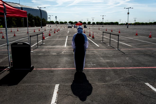 Dignity Health medical worker Angie Roumain waits to direct a car at a drive-up coronavirus testing site at State Farm Stadium from Dignity Health and the Arizona Cardinals in Glendale on Saturday, May 9, 2020.