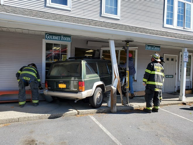 Rhinebeck firefighters examine a car that crashed into a building Saturday morning.