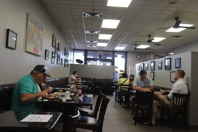 Diners spread out Saturday at Weiss Deli and Bakery in Las Vegas. Gov. Sisolak's implementation of Phase 1 of the state's economic reopening starting Saturday did not bring many diners to the restaurant, and at the outdoor Town Square mall that normally would be thronging with shoppers, many businesses weren't open at all.