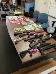 Guns, cash and drugs seized during a bust by Salem police on Thursday.