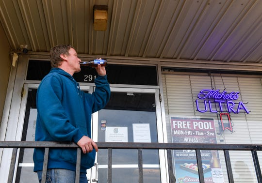 James Whittler drinks a beer while on a smoke break outside the front door of The Nickel Spot on Friday, May 8, in Sioux Falls.