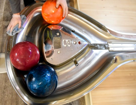 Ethan Strawn disinfects bowling balls on Saturday, May 9, 2020 at Eastway Bowl in Sioux Falls, S.D. The bowling alley recently reopened as COVID-19 restrictions have eased.