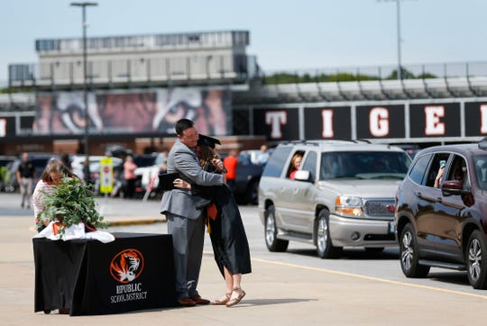Emma Pearce gives her dad Matt Pearce a hug during the Republic High School drive-through graduation ceremony on Saturday, May 9, 2020. The school's commencement was originally scheduled for this weekend but has been postponed to Aug. 1.