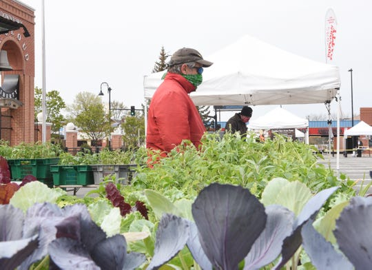 Jon Ness waits for customers at the St. Cloud Area Farmers Market Saturday, May 9, 2020, in downtown St. Cloud.