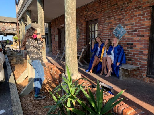 Arden Hunt takes graduation photographs for John Carroll High School students Sophia Glenn, Samantha Godwin and Orla McQuaid Firday, May 8, 2020, outside Waldo's and the Driftwood in Vero Beach.