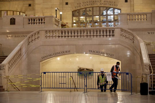 Metro-North Railroad workers emerge from the stairway from the lower level, in an empty Grand Central Terminal, May 1, 2020.
