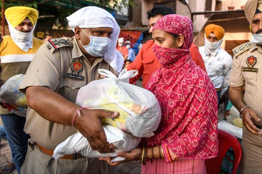 Police personnel distribute grocery items to people in need after the government eased a nationwide lockdown imposed as a preventive measure against the COVID-19 coronavirus,in Amritsar on May 9, 2020.