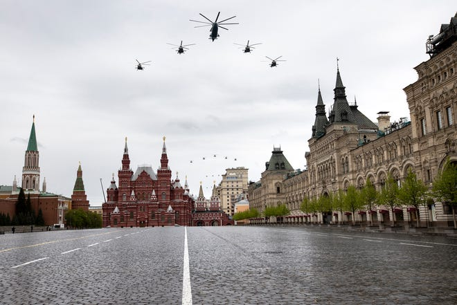 Russian military helicopters fly over over almost empty Red Square to mark the 75th anniversary of the Nazi defeat in World War II in Moscow, Russia, Saturday, May 9, 2020. A massive Victory Day parade on Red Square was canceled due to the coronavirus outbreak, but Russia marked the holiday with the flyby.