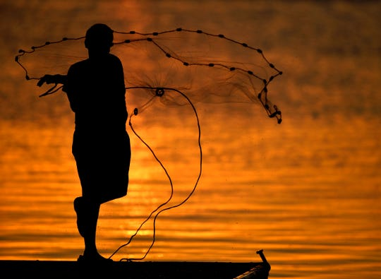 Daniel Chavez, 14, throws a net into the water from a Kirby Lake dock Saturday. Fishing with father Rito Chavez Jr., the pair was having mixed luck as the sun set.