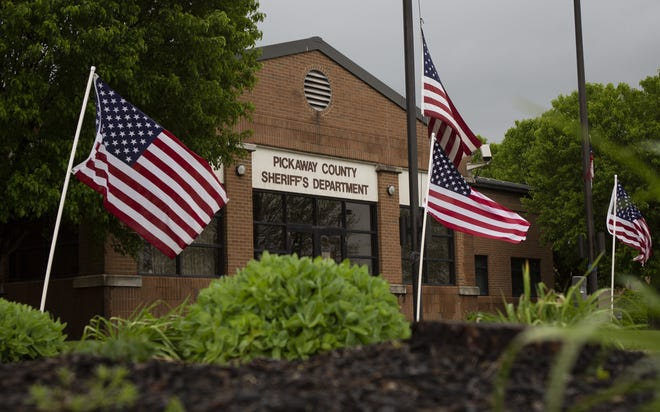 In honor of Dwight Radcliff, the longtime Pickaway County sheriff who passed away earlier this week, flags surround the Pickaway County Sheriff's Office in Circleville on Friday, May 8, 2020. [Adam Cairns/Dispatch]