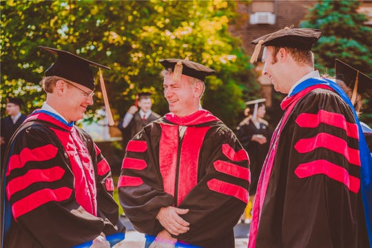Three Ministerial Education Division faculty members talk prior to commencement at God's Bible School & College in Mount Auburn
