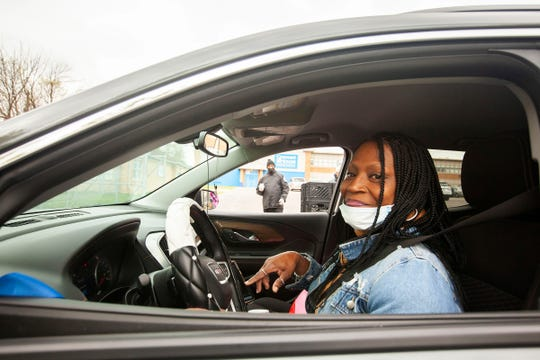 Margaret Lee, board secretary of the superintendent for Covenant House Academy, smiles at the security guard after arriving on the 25th Street campus in Detroit.