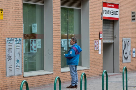 A man looks at notices on the window of an unemployment office April 28 in Madrid, Spain.