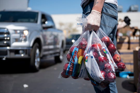 T.J. Robinson, the Cooking Matters coordinator for Gleaners, helps load apples into vehicles during a Gleaners food bank pop-up in cooperation with the Roberto Clemente center, in southwest Detroit, May 6, 2020.